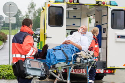 male patient with oxygen mask being transported to an ambulance